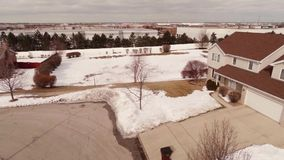 Aerial video of homes in a snow covered suburban neighborhood stock footage