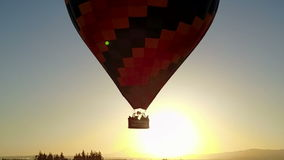 Hot air balloon flying in front of sun. This is an aerial video of a hot air balloon flying in front of sun stock video