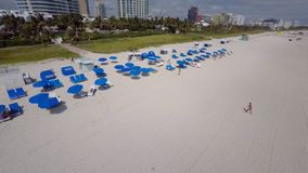 Aerial video Miami Beach blue umbrelllas. 4k aerial drone video Miami Beach with tropical umbrellas on the sand stock video