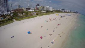 Aerial video Miami Beach blue umbrelllas. 4k aerial drone video Miami Beach with tropical umbrellas on the sand stock video footage