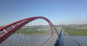 Aerial video photography of a large red Bugrinsky bridge. With cars traveling along it with a lot of cables drawn between the arch that stands over the river Ob stock video