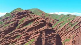 Aerial video of pink rocks with scarce vegetation against blue sky. Aerial shot of pink rocks with scarce vegetation against blue sky stock video footage