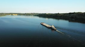 Aerial video river pusher boat transporting barge with dry cargo in middle of summer river, Central Europe stock video footage
