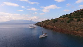 Aerial video shooting, bird`s eye view, wild bay of the Mediterranean Sea, near the Greek island. In the bay, two. Sailing yachts are anchored, a landscape of stock video footage