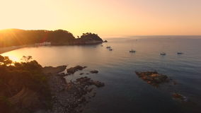 Unspoiled Mediterranean seaside beach aerial drone at sunrise. Aerial video shot in a typical Mediterranean beach landscape. Sailboats sailing in the bay at dawn stock video footage