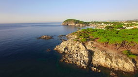 Unspoiled Mediterranean seaside aerial drone view at dawn. Aerial video shot in a typical Mediterranean coast landscape at sunrise. Moving up the rocks with a stock video footage