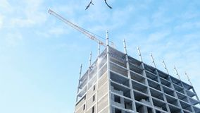 Aerial video side view of under construction multi-storey building of blocks in sky background. Camera is static stock footage