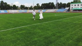 Aerial video, at the stadium, in the center of a green football field, happy newlyweds in wedding attire are running. Through the field. spring sunny day stock video