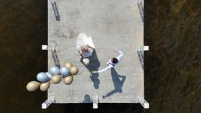 Aerial video, top view, beautiful newlywed couple, bride and groom dancing outdoors, on a pier, groom holds balloons in stock footage
