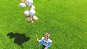 Aerial video, top view, at the stadium, in the center of a green football field, happy boy with balloons is runing. Through the field. spring sunny day stock footage