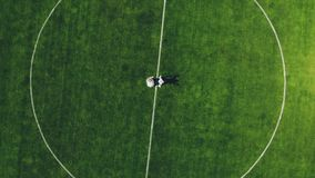 Aerial video, view from the top, in the stadium, in the center of a green football field, newlyweds in wedding attire. Dancing, spinning stock footage