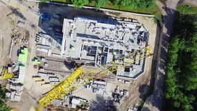 Aerial videography, top view of the construction site, a construction crane works, builders build a house.  stock video