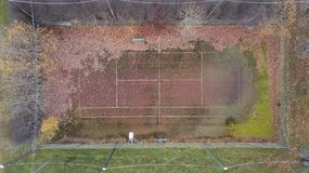 Aerial view of abandoned tennis field. High angle view of an abandoned tennis field in autumn with alot of leafs Royalty Free Stock Photo