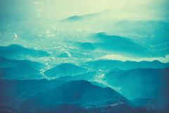 Aerial view above Alpine mountains. Alps background. Aerial view above Alpine mountains. Alps blue background stock photo
