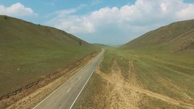 Aerial view above bus and car driving along empty countryside road between hills on sunny day. Drone, green grass, blue sky, clouds stock video footage