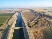 Aerial view above California aqueduct. Running through almond plantations and cultivated fields, drone shoot of farmland landscape Stock Images