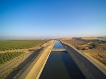 Aerial view above California aqueduct. Running through almond plantations and cultivated fields, drone shoot of farmland landscape Stock Photos