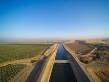 Aerial view above California aqueduct. Running through almond plantations and cultivated fields, drone shoot of farmland landscape Stock Photo