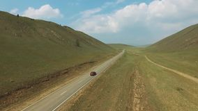 Aerial view above cars driving along empty countryside road between hills on sunny day. Drone, green grass, blue sky, clouds stock footage