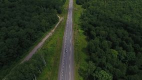 Aerial view above cars driving along empty countryside road on sunny day. Drone, green grass, blue sky, clouds stock video