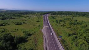 Aerial view above cars driving along empty countryside road on sunny day. Drone, green grass, blue sky, clouds stock footage