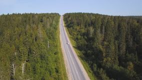 Aerial view from above of country road through the green summer forest in summer. Shot. Car driving. High angle view of stock photography