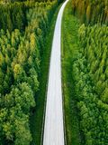 Aerial view from above of country road through the green summer forest in summer Finland. Drone photography Royalty Free Stock Photography