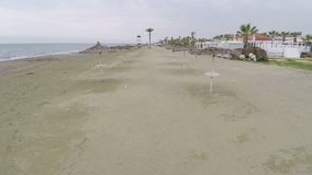 Aerial view above empty beach with straw parasols, deserted coastline in Cyprus. Stock footage stock video footage