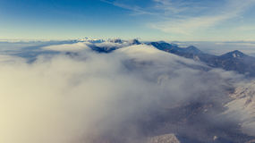 Aerial view above mountain ridge with river of clouds. Royalty Free Stock Photo