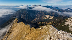Aerial view above mountain ridge with river of clouds. Stock Photos