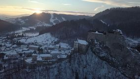 Aerial view above Orava castle in sunset winter evening, Slovakia. Flying above historical Orava castle in Slovakia in sunset winter evening. Aerial view of tilt stock video