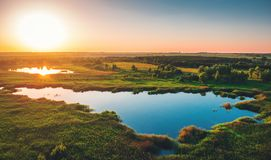 Aerial view above summer forest and lake at sunset, beautiful nature landscape panorama stock images