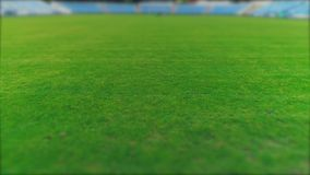Aerial view of accurately cut grass, lawn in the football field, inside a bif stadium. 4K. Low aerial view of blurred grass in a stadium. Copy space stock video footage