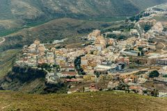 Aerial view of Adeje town on the soth coastline at sunny day. Beginning of famous Hell gorge. Rocky tracking road in dry mountain. Area. Tenerife, Canary Island stock photo