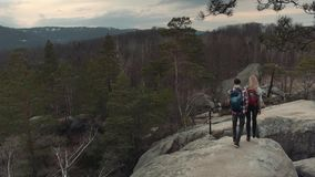 Aerial view of adorable couple with stylish backpacks holding hands and walking on rock alps. Dangerous precipice. Extreme activities. Amazing nature on the stock video