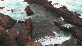 Aerial view from afar - a person stands on the edge of a rock of volcanic origin, the ocean coast. Tenerife, Spain