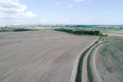 Aerial view on agricultural field with rural road across Royalty Free Stock Photography