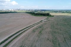 Aerial view on agricultural field with rural road across Royalty Free Stock Photos