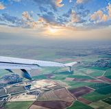 Aerial view through airplane porthole. With detail of aircraft wing Royalty Free Stock Photos
