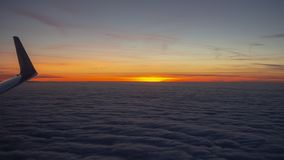 Aerial view from the airplane to a massive sea of clouds at the sunset royalty free stock images