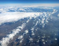 Aerial view from the airplane window. We see the earth through the clouds Royalty Free Stock Photos