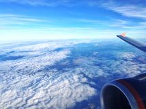 Aerial view from an airplane. With wing, engine and fluffy clouds Stock Photos