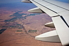 Aerial View of Airplane Wing Over Land Stock Images