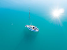 Aerial view of alone yacht sailling on azure water. Beautiful aerial view of alone yacht sailling on azure water Stock Photography