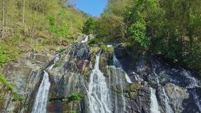 Aerial View along River Cascade with Great Waterfall. Aerial view along river cascade with large high waterfall between rocks among wild tropical woods stock footage
