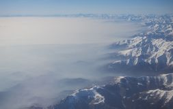 Aerial view of the Alps in Europe during winter season with fresh snow and fog covers the Po plain Stock Images