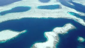 Aerial View of Amazing Coral Reefs in Raja Ampat. An aerial view shows vast coral reef growing in the Dampier Strait of Raja Ampat, Indonesia. This remote region stock video footage