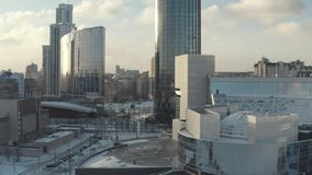 Aerial view of amazing futuristic glass skyscrapers in the center of big city against blue cloudy sky. Action. Modern. Aerial view of amazing futuristic glass stock footage