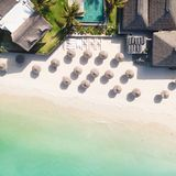 Aerial view of amazing tropical white sandy beach with palm leaves umbrellas and turquoise sea, Mauritius. royalty free stock photos