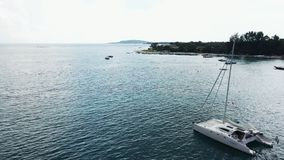 Aerial View of a Anchored Catamaran Yacht Standing and people can Sunbathing on it`s Deck. stock footage